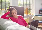 Woman using laptop on sofa