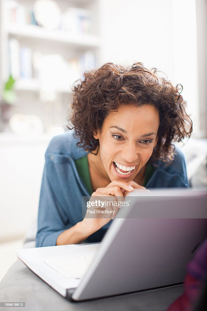 Woman using laptop on sofa : Stock Photo
