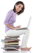 Woman using laptop on stack of books