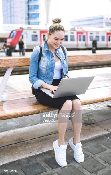 Woman using laptop on the railroad station