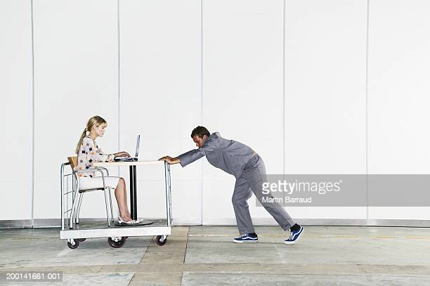 Woman using laptop on trolley pushed by man, side view