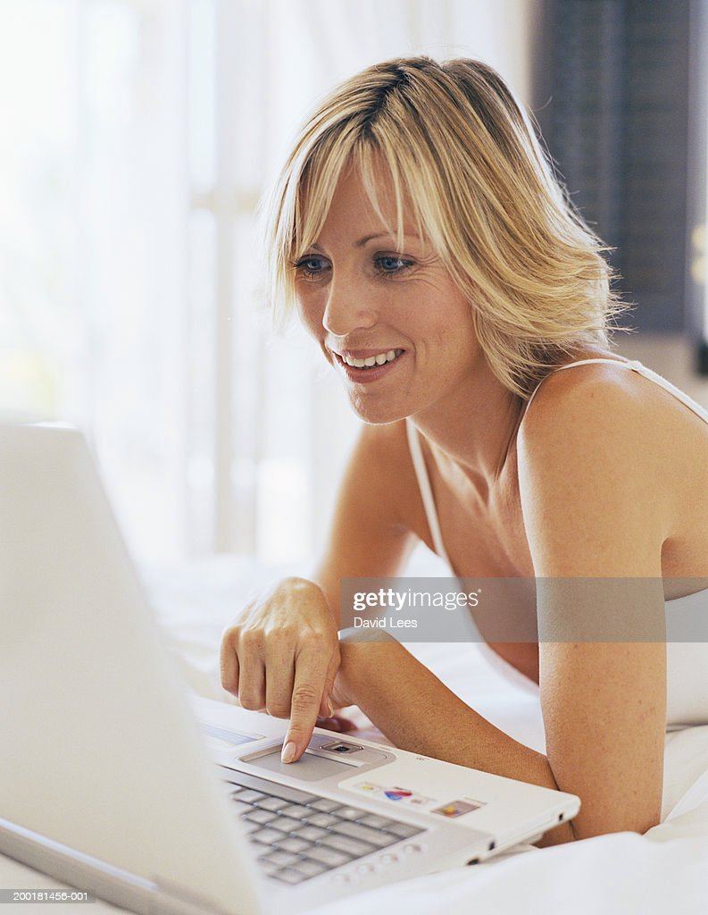 Woman using laptop, smiling, close-up : Stock Photo