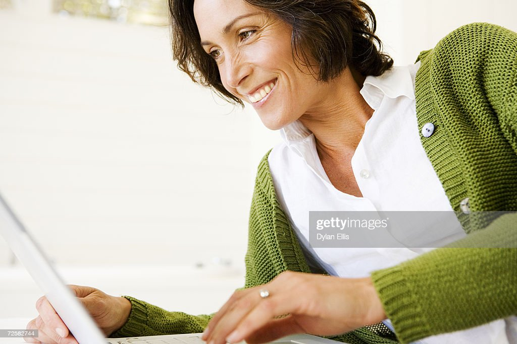 Woman using laptop, smiling : Stock Photo