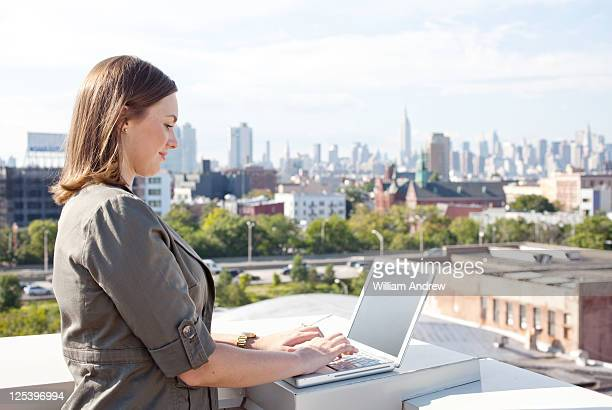 Woman using laptop, urban skyline in background