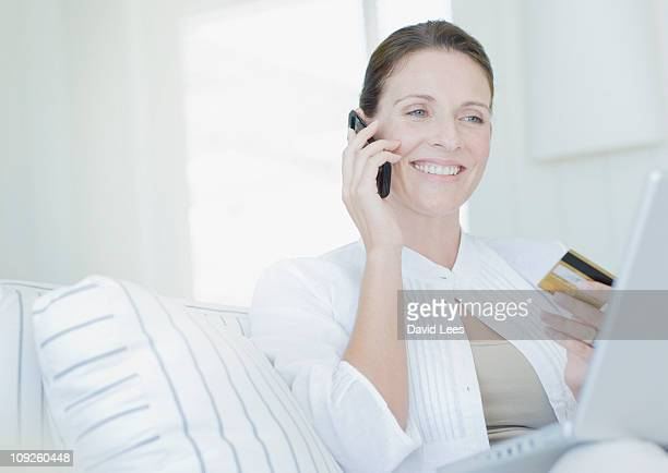 Woman using laptop while holding credit card