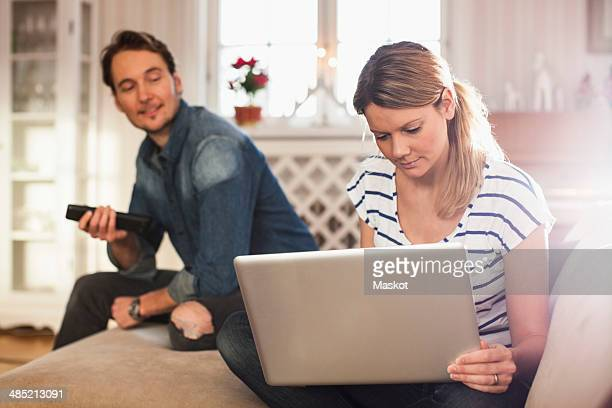 Woman using laptop while man looking at her in house