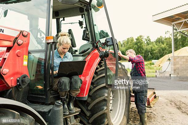 Woman using laptop while man standing by tractor