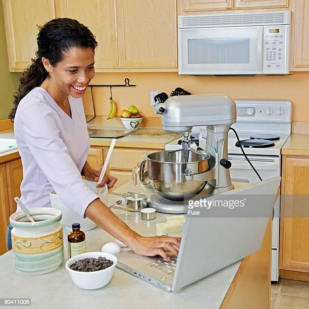 Woman Using Laptop While Preparing Food