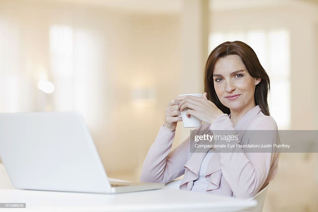 Woman using laptop with cup of coffee : Stock Photo
