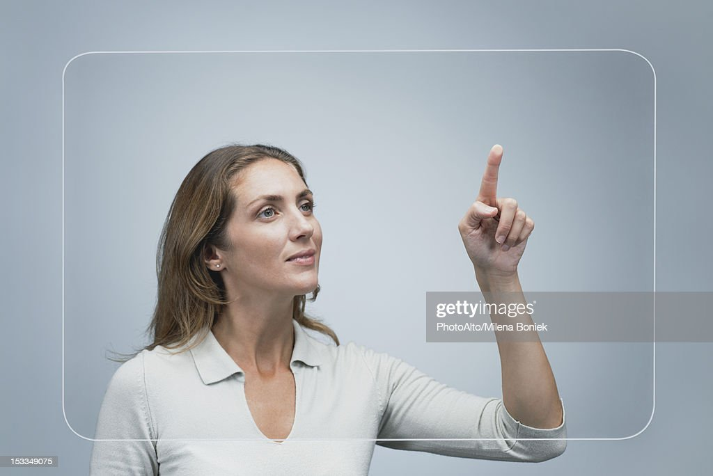 Woman using large transparent touch screen