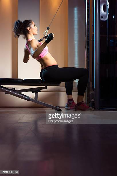 Woman using lat pulldown machine at the gym