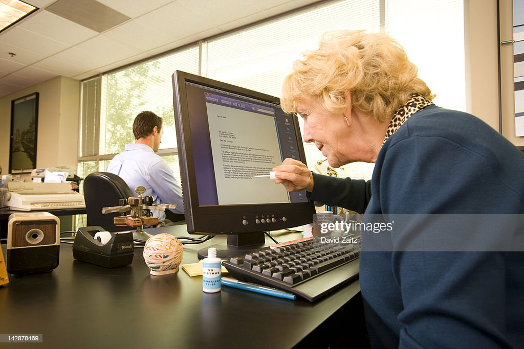 Woman using liquid correction fluid on computer : Stock Photo