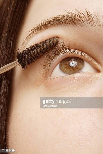 Woman using mascara brush, close-up of eye