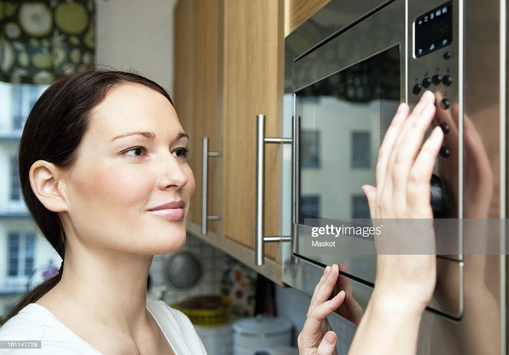 Woman using microwave oven : ストックフォト