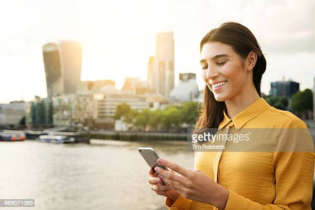 Woman using mobile at sunset