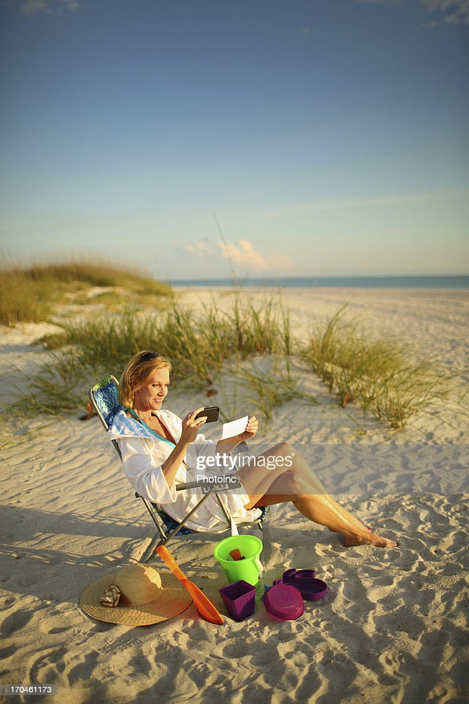 Woman using mobile deposits while relaxing on beach