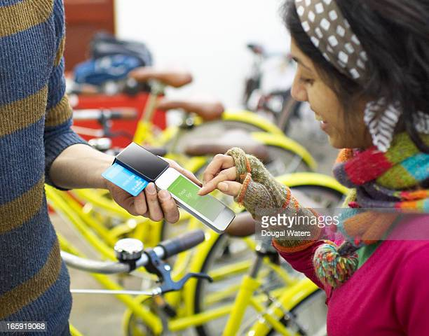 Woman using mobile payment device in bike shop.