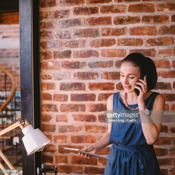 Woman Using Mobile Phone Against Brick Wall
