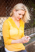 Woman using mobile phone against chain link fence