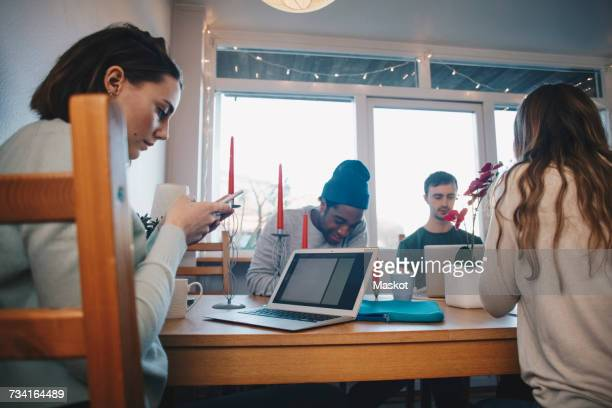 Woman using mobile phone by friends studying in dorm room
