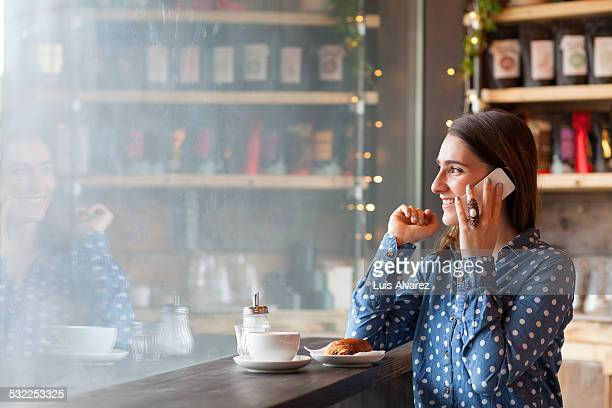 Woman using mobile phone in coffee shop