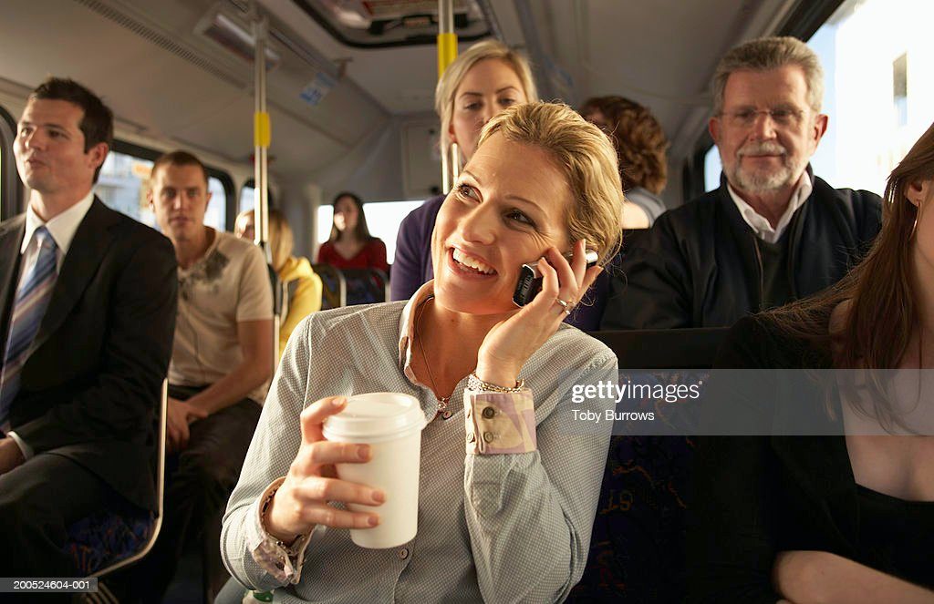 Woman using mobile phone on bus, smiling : Stock Photo
