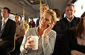 Woman using mobile phone on bus, smiling