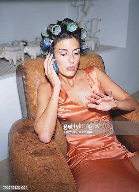 Woman using mobile phone, rollers in hair, blowing on nails