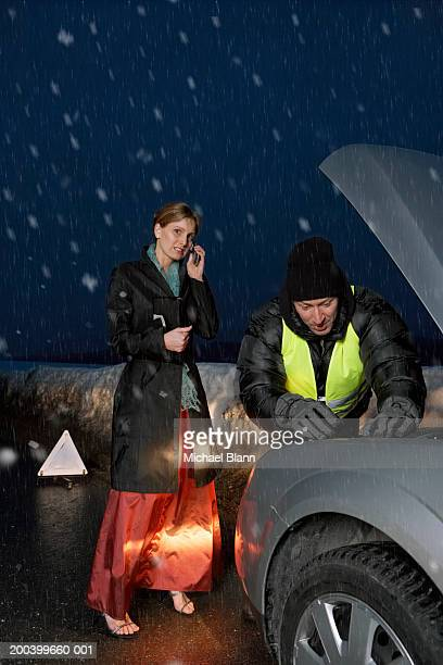 Woman using mobile phone  standing by mechanic working on car in snow