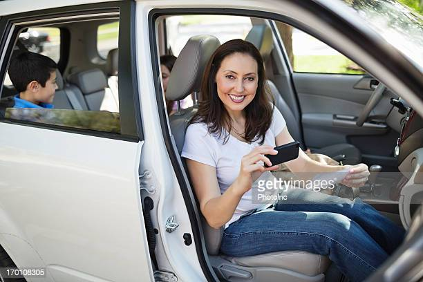 Woman Using Mobile Phone To Deposit Check In Car