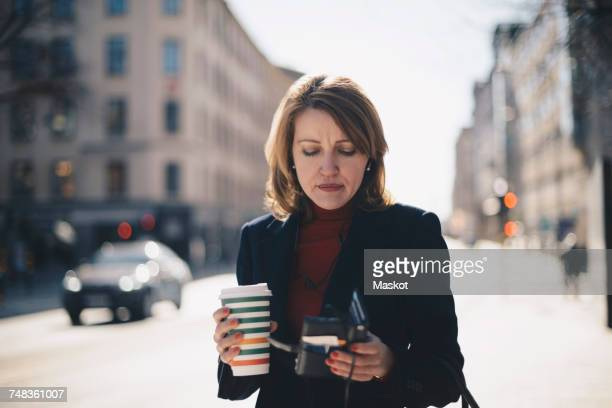Woman using mobile phone while having coffee in city on sunny day during winter