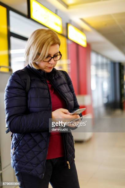 Woman using mobile phone while waiting for a flight