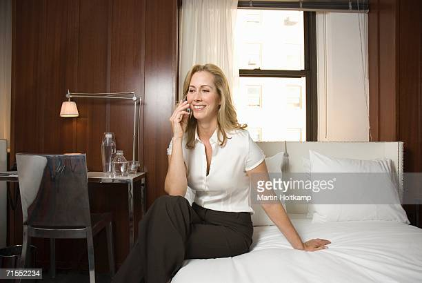 Woman using mobile phone whilst sitting on bed in hotel room