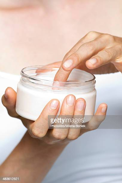 Woman using moisturizing cream
