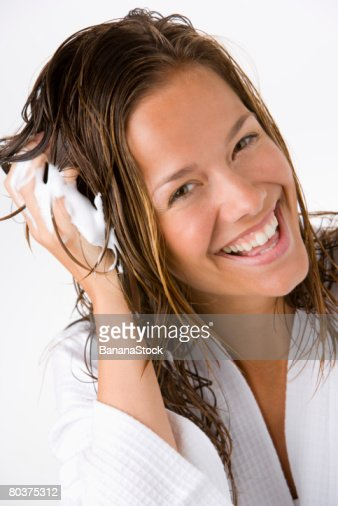 Woman using mousse in hair : Stock Photo