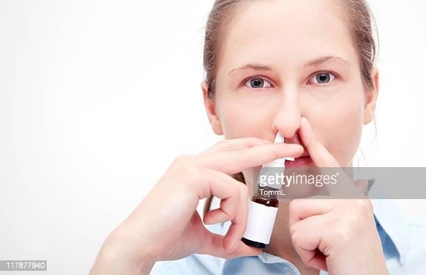 Frau mit Nasenspray und hält andere nostril geschlossen.