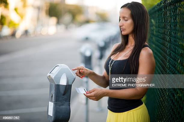 Woman using parking meter