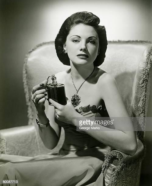 Woman using perfume in armchair, portrait