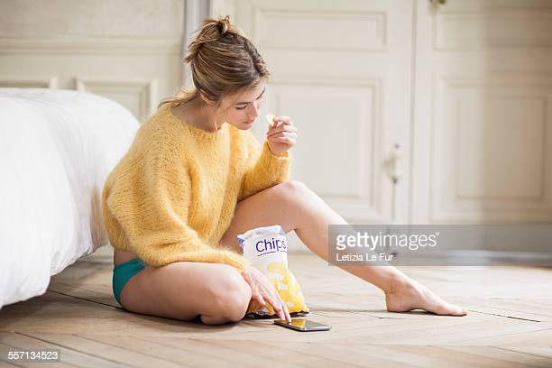 Woman using phone and eating chips