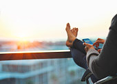 Woman using phone and relaxing at end of the day with feet up
