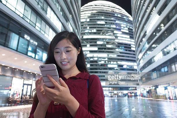 Woman using phone at city night