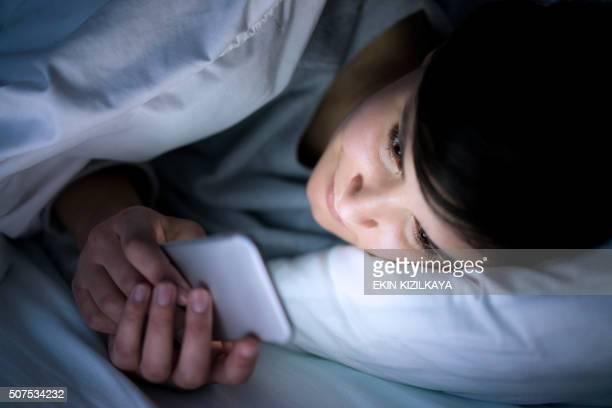 Mujer usando el teléfono en la cama