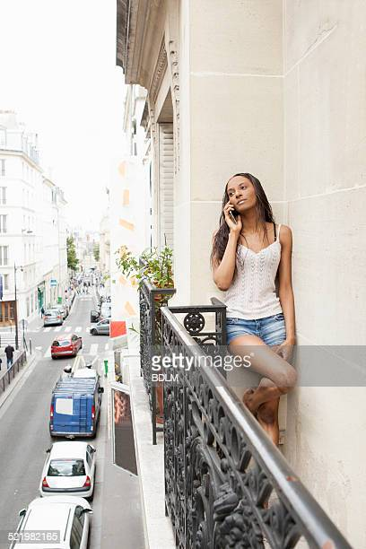 Woman using phone on balcony, Paris, France