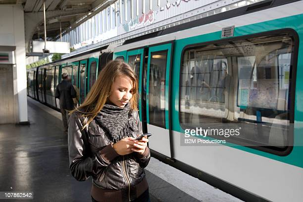 Woman using phone on subway platform