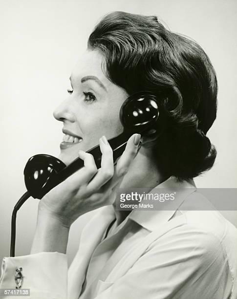 Femme à l'aide de téléphone, posant en studio, (B & W) (gros plan