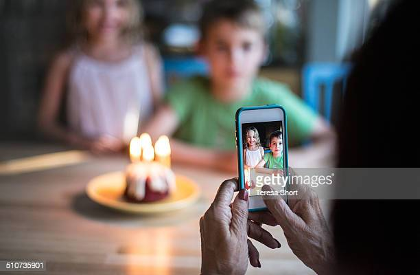 Woman Using Phone to Photograph Kids at Birthday