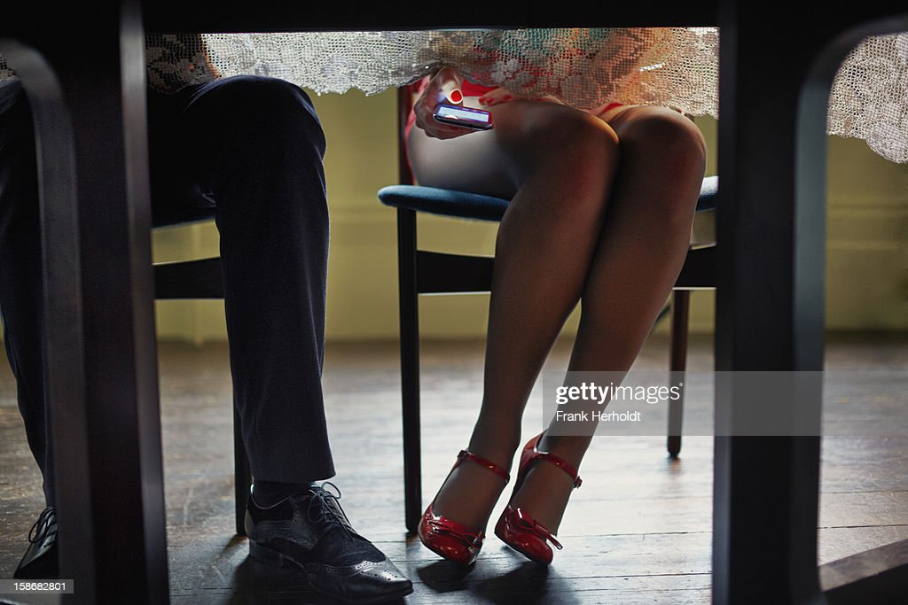 Woman using phone under table : Stock Photo
