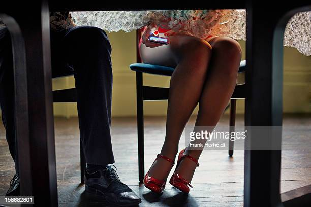 Woman using phone under table