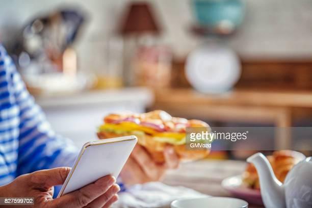 Femme à l'aide de téléphone tout en prenant son petit déjeuner