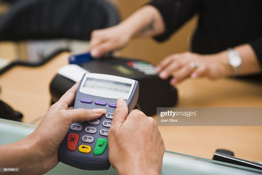 Woman using pin pad while store owner swipes card